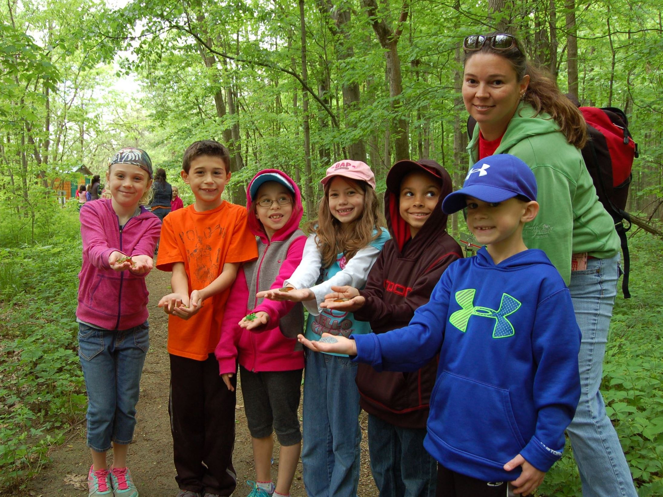 children with naturalist in woods